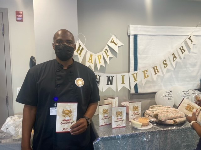 Employee standing in front of Happy Anniversary table